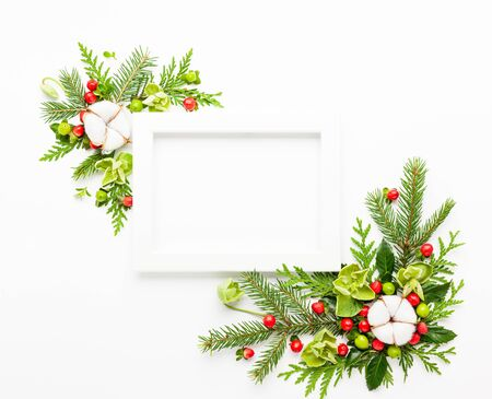 Christmas composition  with photo frame, cotton flower, branches of spruce and holly with red berries on white background. Merry christmas greeting card with empty space for holiday text. Flat lay