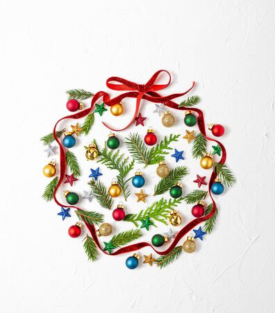 Christmas composition  with red ribbon ,branches of fir tree and Christmas ornaments in shape of Christmas bauble on white background. Merry christmas greeting card with empty space for holiday text. Flat lay Imagens