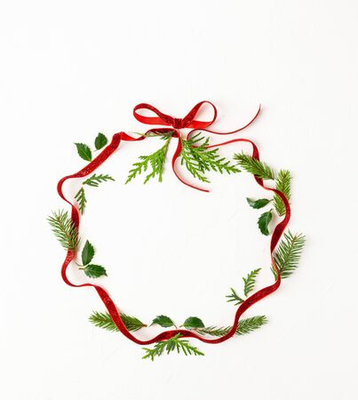 Christmas composition  with red ribbon, branches of spruce and holly with red berries in shape of Christmas bauble on white background. Merry christmas greeting card with empty space for holiday text. Flat lay