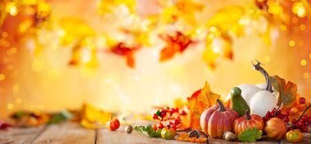 Fondo de otoño de hojas caídas y calabazas en mesa de madera vintage. Concepto de otoño con fondo de hojas rojo-amarillo. Calabazas de Acción de Gracias.
