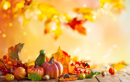 Autumn background from fallen leaves and pumpkins on wooden vintage table. Autumn concept with red-yellow leaves background. Thanksgiving pumpkins. Imagens