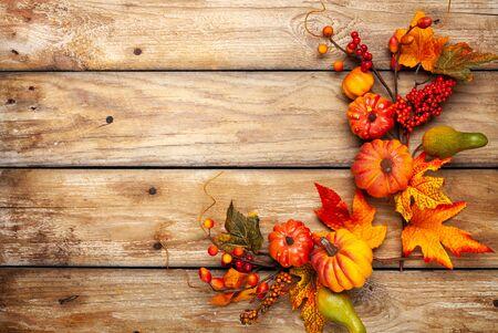 Festliche Herbstdekoration aus Kürbissen, Beeren und Blättern auf rustikalem Holzhintergrund. Konzept von Thanksgiving oder Halloween. Flache Herbstkomposition mit Kopienraum. Standard-Bild
