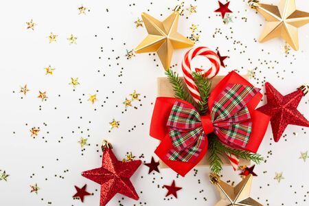 Christmas gift box with red ribbon and candy cone on white background. Top view. Stock Photo