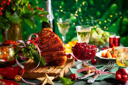 Glazed roast ham with cloves,sparkling wine and traditional vegetables dishes for Christmas dinner.