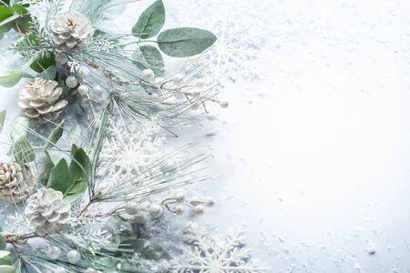 Concepto de vacaciones de Navidad y año nuevo con ramas de abeto nevado y piña sobre fondo claro. Tarjeta de felicitación de Navidad, vista superior.