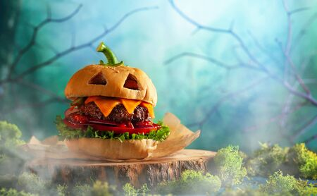 Halloween party burger in shape of scary pumpkin  on natural wooden board. Halloween food concept.