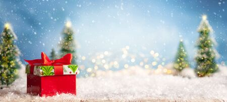 Bellissimo sfondo invernale con scatole regalo rosse su una vecchia scrivania in legno, abeti e cielo blu. Concetto di inverno, Capodanno e Natale con sfondo innevato. Archivio Fotografico