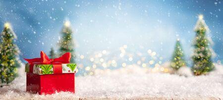 Schöner Winterhintergrund mit roten Geschenkboxen auf einem alten hölzernen Schreibtisch, Tannenbäumen und blauem Himmel. Winter-, Neujahrs- und Weihnachtskonzept mit schneebedecktem Hintergrund. Standard-Bild