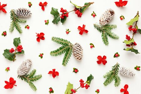 Christmas background with pine cones, branches of holly with red berries and fir tree on white. Winter festive nature concept. Flat lay, copy space. 写真素材