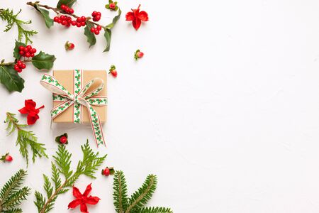 Christmas background with gift box, branches of fir tree, evergreens and holly with red berries on white. Winter festive nature concept. Flat lay, copy space. 写真素材