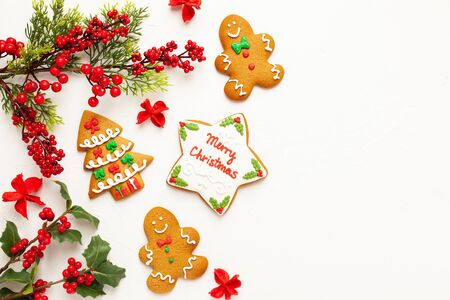 Christmas background with gingerbread cookies and branches of holly with red berries on white. Winter festive nature concept. Flat lay, copy space.