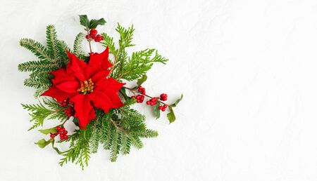 Christmas decoration with poinsettia flowers and holly berry on white background. Festive winter holiday concept. Flat lay.