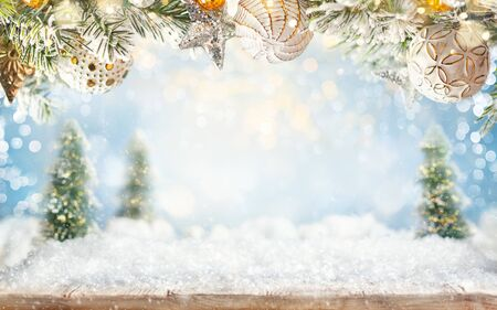 Beautiful winter background with Christmas ornaments, wooden old desk, fir trees and blurred blue sky. Winter, New Year and Christmas concept with snowy background.