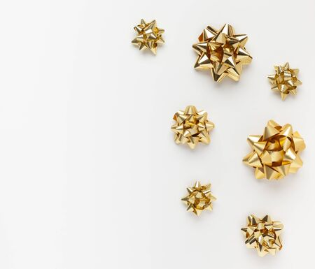 Christmas or New Year composition with gold sparkling ribbon decorations on white background. Flat lay and copy space.