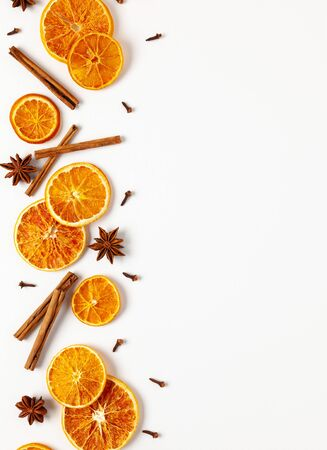 Christmas composition with dried oranges and spices on white background. Natural food ingredient for cooking or Christmas decor for home. Flat lay, copy space. Zdjęcie Seryjne