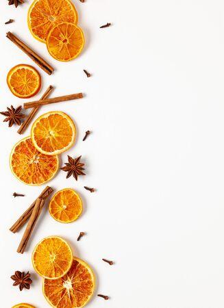 Weihnachtskomposition mit getrockneten Orangen und Gewürzen auf weißem Hintergrund. Natürliche Lebensmittelzutat zum Kochen oder Weihnachtsdekoration für zu Hause. Flach legen, Platz kopieren.