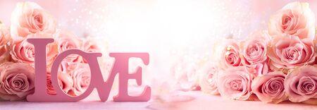 """与粉红玫瑰和词""""爱""""的节日静物画。与玫瑰的花构成。软焦点。"""
