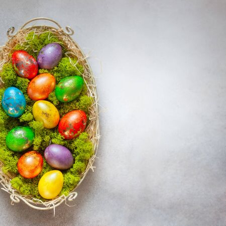 Easter composition with colorful Easter eggs on moss in vintage tray. Top view. Easter card with copy space for text.