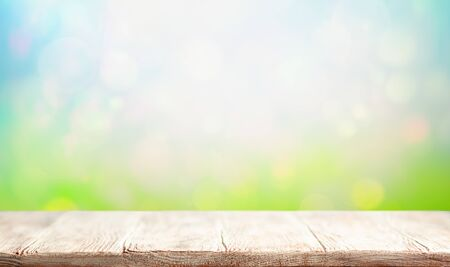 Wooden table and blurred green spring or summer background. Easter natural background with copy space.
