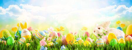 Oeufs de Pâques, lapin et fleurs de printemps sur le pré. Notion de Pâques. Fond de printemps ou d'été avec de l'herbe fraîche sur fond de ciel bleu avec espace de copie.