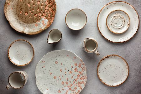 Set of ceramic round bowls, plates and sauce boats on a vintage grey background. Flat lay, top view. Stockfoto