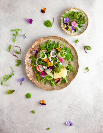 Delicious summer salad with edible flowers, vegetables, fruit, microgreens and cheese. Clean and healthy eating concept. Top view.