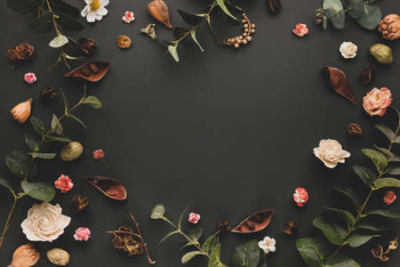 Autumnal-winter concept with dried flowers, branches of eucalyptus, leaves and berries on dark background. Frame of plants. Flat lay, copy space.