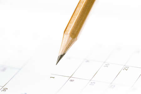 Closeup of sharp graphite pencil on white paper of calendar. Concept of The National Day of Knowledge or planning for business meeting.