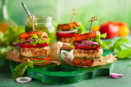 Delicious roasted pumpkin turkey burger with tomatoes and pesto on green wooden board.