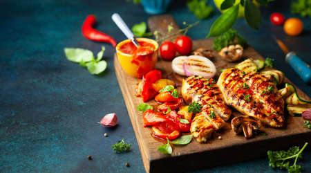 Grilled chicken breasts and different vegetables ad mushroom cooked on a BBQ served on wooden board. Close up view. Concept homemade summer barbeque dinner