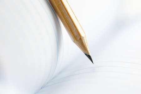 Closeup of sharp graphite pencil on white paper of notebook. Concept of The National Day of Knowledge or International literacy day. Standard-Bild
