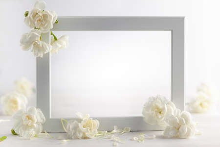 Still life with white flowers and frame on light backdrop. Creative concept for celebration of mother day, birthday, wedding or Valentines day Standard-Bild