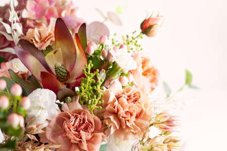 由美丽的花朵和浆果组成的秋天的构图在灯光的背景下。植物区系装饰。天然植物的背景。