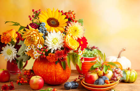 Concept of autumn festive decoration for Thanksgiving day. Autumn bouquet of flowers and berries in a pumpkin on a table, different fruits and pumpkins.
