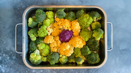 Different colorful cauliflower florets in baking dish before cooking Cabbage gratin. Concept healthy eating.