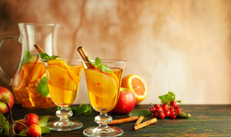 Apple cider cocktail with red oranges and spices in glasses and jug on table. Concept of autumn and winter drinks. 写真素材