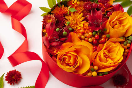 Festive composition with beautiful flowers and berries in red round box on white background. Flat lay, copy space.