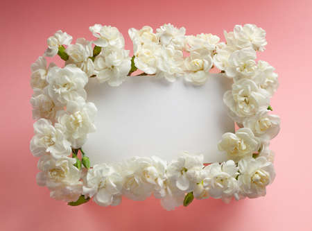 Festive flowers frame made of white carnations on pastel pink background with empty greeting card. Flat lay, top view.