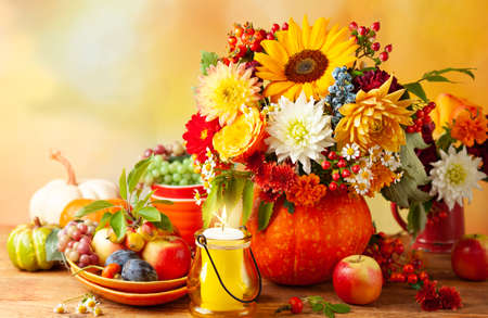 Concept of autumn festive decoration for Thanksgiving day. Autumn bouquet of flowers and berries in a pumpkin on a table, different fruits and pumpkins. 写真素材