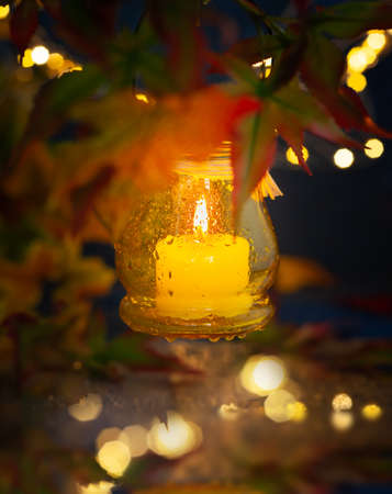 Festive autumn lighting decor. Candle in a jar with rain drop, hanging on tree branches for night decoration.