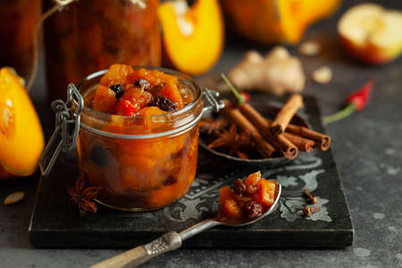 Homemade pumpkin and apple chutney with raisins in jars on a table. Delicious sweet spicy sauce preserved for autumn and winter season.