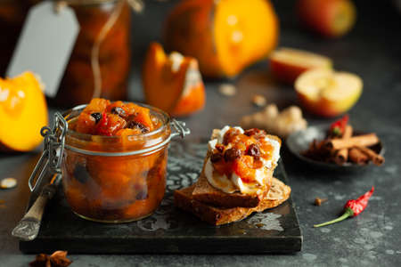 Homemade pumpkin and apple chutney with raisins in jars and on toast bread. Delicious sweet spicy sauce preserved for autumn and winter season. 写真素材