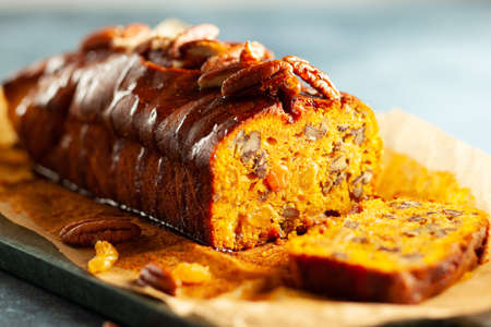 Delicious pumpkin pecan and raisin cake on cutting board. Loaf of pumpkin bread. 写真素材
