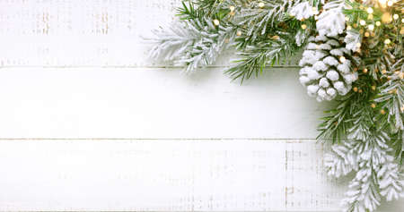 Christmas tree branch and pine cone in snow on a white wooden background. Winter festive concept. Flat lay, copy space. Banque d'images