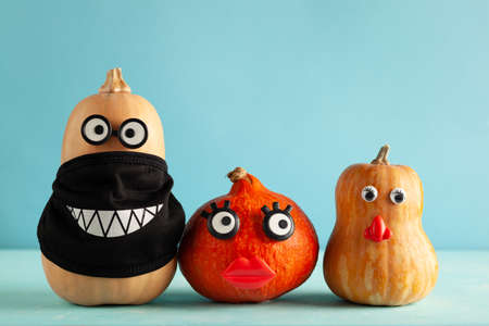 Funny pumpkins with faces and in a black protective mask on pastel blue background. Concept celebration of Halloween or Thanksgiving