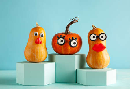 Funny pumpkins with faces on pastel blue background with copy space. Concept celebration of Halloween
