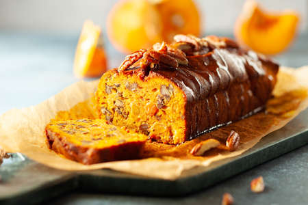 Delicious pumpkin pecan and raisin cake on cutting board. Loaf of pumpkin bread. Imagens