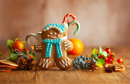 Christmas gingerbread cookies with Christmas decorations on wooden background. Traditional Christmas baking.