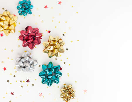 Christmas or New Year composition with colored sparkling ribbon decorations on white background. Flat lay, copy space. 免版税图像