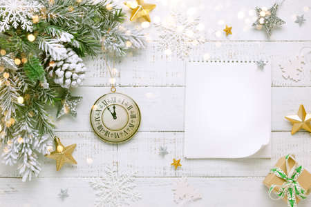 Christmas tree branch with pine cone in snow, retro style clock and notebook on a white wooden background. Winter or Christmas festive concept. Flat lay, copy space. 免版税图像